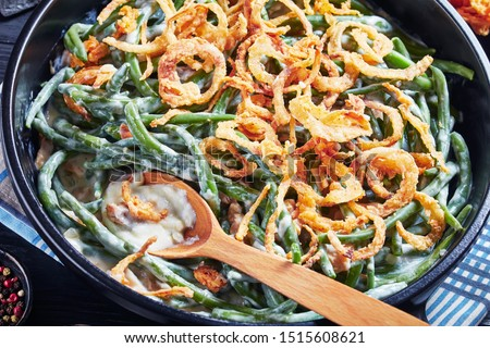 Photo of  close-up of Green Bean Casserole topped with crispy fried onions in a black dish with spoon,  american cuisine, view from above
