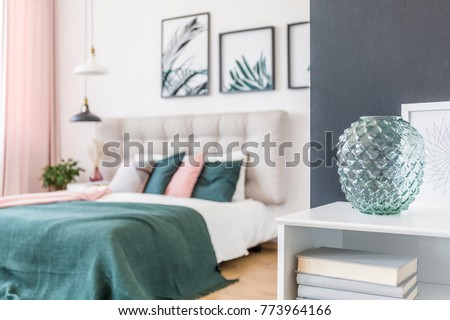 Close-up of green glass vase on white shelf with books in green bedroom interior with lamps and gallery of posters