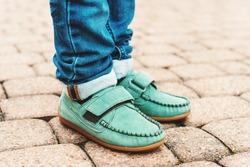 Close up of green moccasins on child's feet