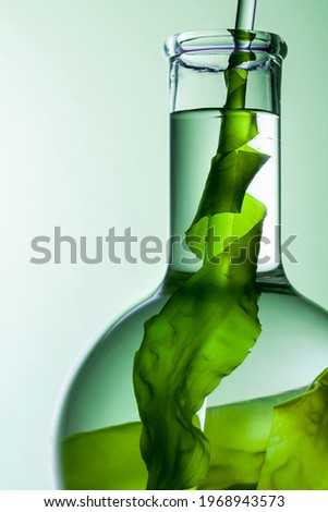 close up of green seaweed with glass rod in flask on green background.