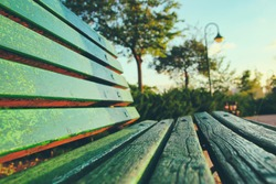 close up of green wooden bench in urban park during sunset time