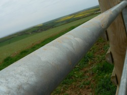 Close up of grey round metal pole (beam or bar) at the top of a gate or fence in the countryside. Tiny marks of rust; farmland, fields and hills in the background