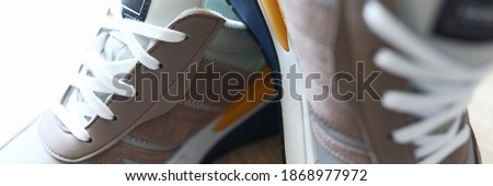 Close-up of grey sneakers on table. Sport footwear for running and fitness. Amazing and trendy pair of shoes. Active lifestyle. Nice texture with white sole and laces Photo stock ©