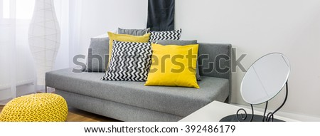 Close Up Of Grey Sofa With Decor Cushions In Black Yellow Grey And