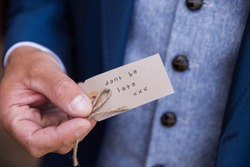 Close up of grooms hand on wedding day holding sign saying