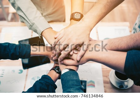Close up of  group of business people joining their hands together in unity.