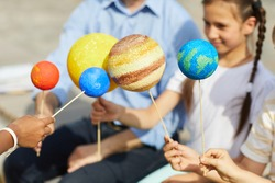 Close up of group of children holding model planets while enjoying outdoor astronomy lesson in sunlight, copy space