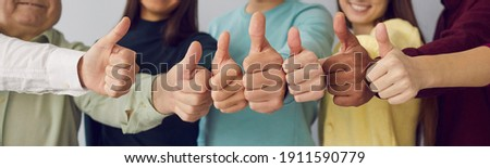 Close up of group of diverse people showing raised thumbs at camera as gesture of recommendation or good choice. Professional multicultural team demonstrates satisfaction and gives a positive response