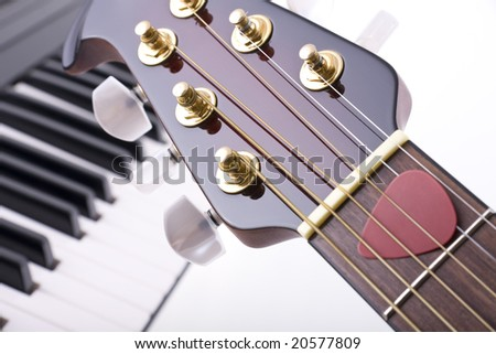 Close up of guitar head and keyboard - abstract music concept