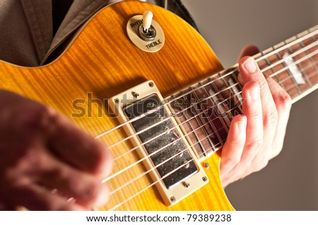 Close up of guitar with hand