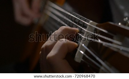 Close up of guitarist hand playing acoustic guitar. Close up shot of a man with his fingers on the frets of a guitar playing stock photo