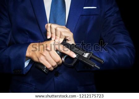 Close up of gunman in businessman suit reloading pistol in hands. #1212175723