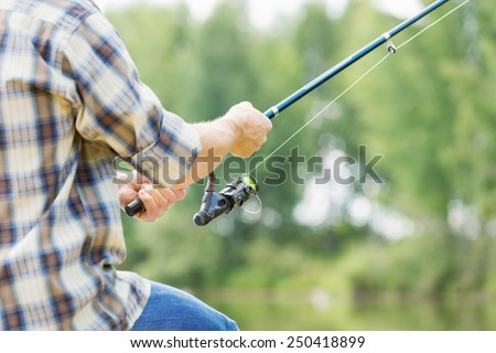 Close up of guy sitting on bridge and fishing