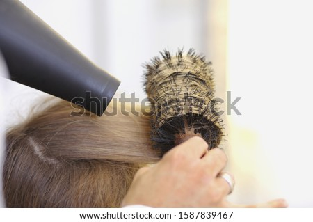 Close up of hair stylist blowdrying client's hair with round brush