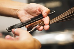 Close-up of hairdresser male hands during cutting female hair