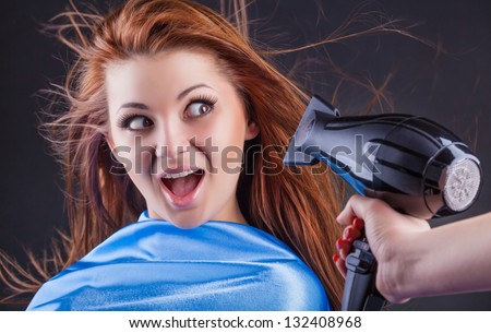 Close up of hairdressers hands drying long hair with blow dryer on a dark background