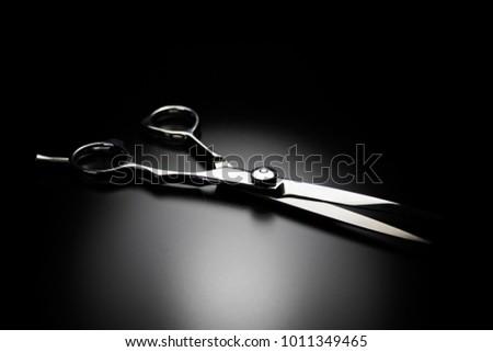 Close up of hairdressing scissor on black background. Shiny chrome barber scissors.