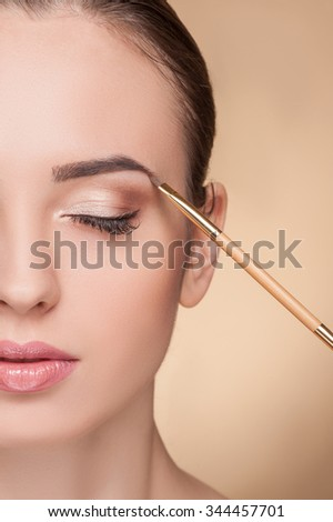 Close up of half of the female face. The beautiful woman is getting make up by artist. The beautician is touching a brush to her eyebrow. The girl closed eyes with calmness