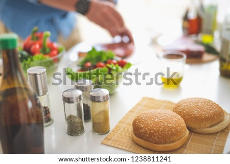 Close up of hamburger bun with sesame seeds, bottles with cumin, ground cloves and pepper on table. Vegetables and male hands cooking meat on blurred background #1238811241