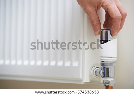 Shutterstock Close Up Of Hand Adjusting Heating Thermostat