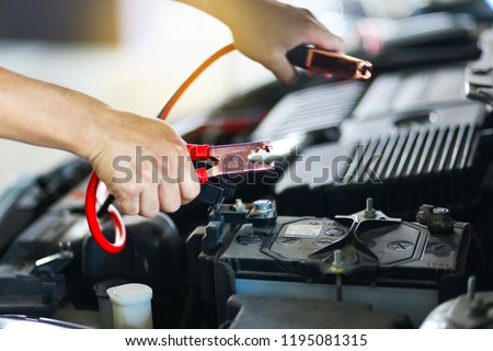 Close up of hand Charging car battery with electricity trough jumper cables.