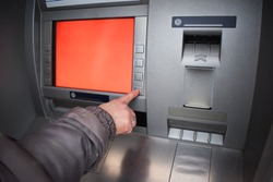 Close up of hand entering pin at an ATM. Female arms, ATM - entering pin.Woman using banking machine.