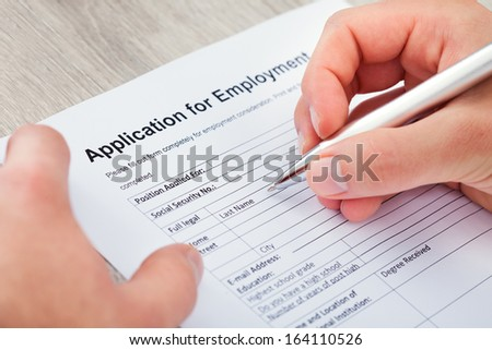 Close-up Of Hand Filling Application For Employment