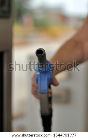 Close-up of hand held fuel pump gun. End of fossil fuels and new energies #1544901977