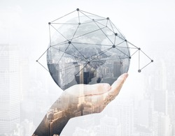 Close up of hand holding abstract globe with connections on city background. Global business concept. Double exposure