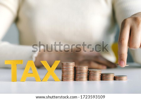 Close-up Of Hand holding coin putting on  stacked Coins and word tax on white table. Income Tax Raise Concept Photo stock ©
