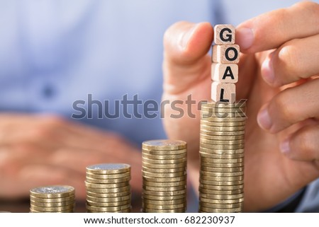 Close-up Of Hand Holding Goal Blocks Over The Increasing Coin Stack #682230937