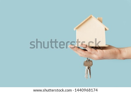 Close-up of hand holding keys and wooden house model against blue background