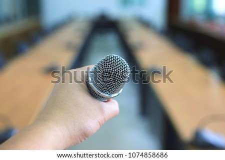 Close-up of hand holding microphone in meeting room selective focus and shallow depth of field #1074858686