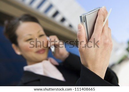 Close up of hand holding palmtop and stylus while woman on a call