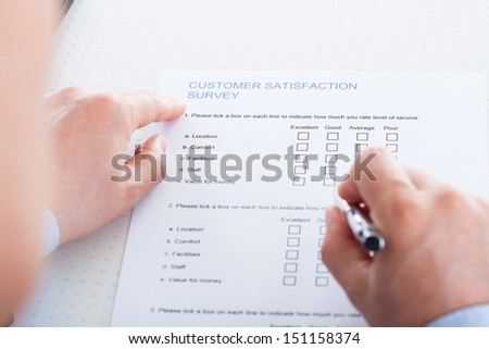 Close-up Of Hand Holding Pen Over Blank Check Box In Application Form