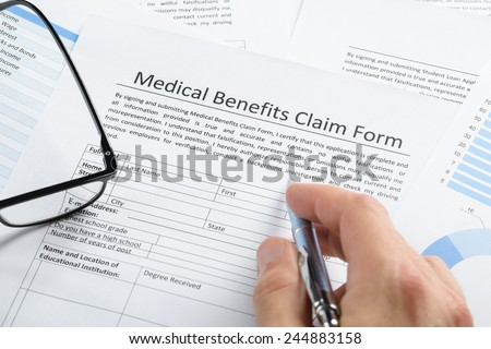 Close-up Of Hand Holding Pen Over Medical Claim Application Form
