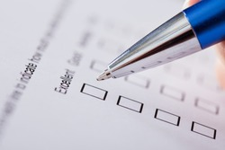 Close-up Of Hand Holding Pen Over Survey Form