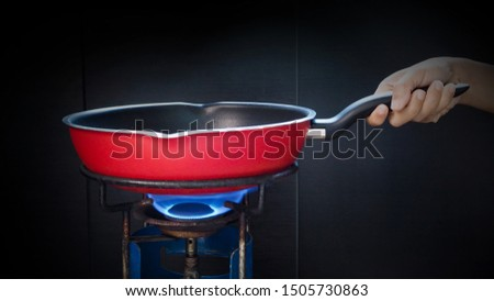 close-up of hand holding red frying pan on retro and old rustic gas stove with flame on stove top for cooking. #1505730863
