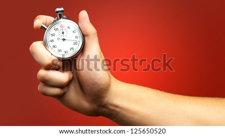 Close Up Of Hand Holding Stopwatch against a red background - stock photo