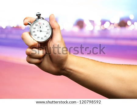 Close Up Of Hand Holding Stopwatch at a city by night