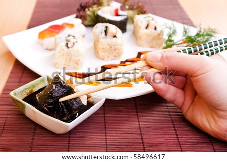 close-up of hand holding sushi roll with chopsticks and dipping