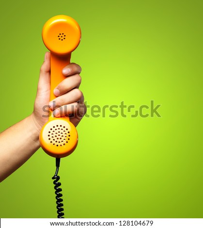 Close Up Of Hand Holding Telephone against a green background