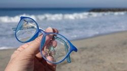 Close up of hand holding up a ruined, scratched and sandy pair of blue prescription glasses lost on beach