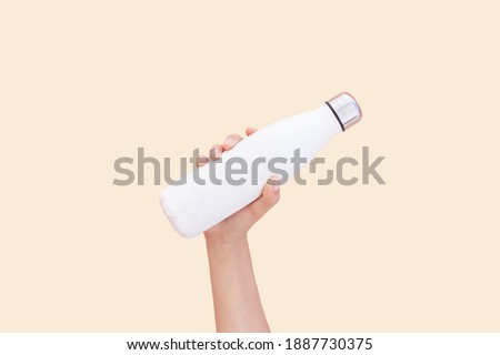 Close-up of hand holding white reusable steel thermo water bottle isolated on background of set sail champagne color, 2021 trend; with copy space. Photo stock ©