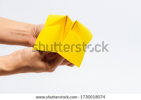 Close up of hand in a paper fortune teller isolated on white background. Stock foto ©