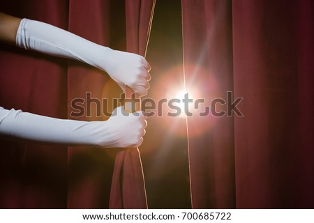 Close-up of hand in a white glove pulling curtain away