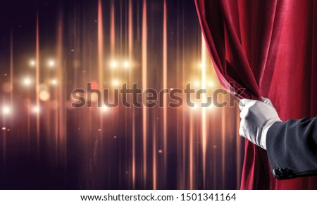 Close up of hand in white glove open red velvet curtain to stage Foto stock ©