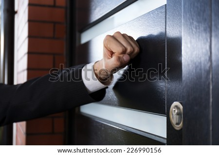 Close-up of hand knocking on the door Foto d'archivio ©