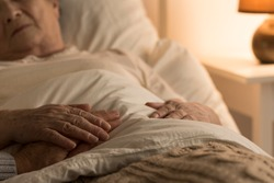 Close-up of hand of a senior on the hand of dying elderly person as a sign of support during sickness