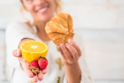 close up of hand of woman holding an orange and strawbberry and in the oter hand a croissant - dieting and healty lifestyle and concept